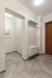 Spacious hallway with white walls. Photo of spacious hallway with white walls and grey floor Stock Photo