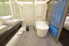 Spacious Hotel Suite Bathroom with sliding door. This is a spacious toilet, bath and shower room with double basin & window, freestanding standalone bathtub and stock photo