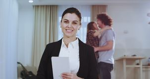 In a spacious house a real estate agent womna very beautiful looking seriously to the camera and holding a tablet then. Smile very large with a perfect teeth stock video footage