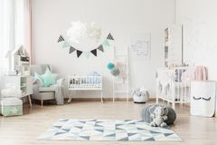 Spacious kid`s room with banner. Grey pouf and plush toy on geometric carpet in spacious kid`s room with banner and paper bag for toys Stock Photos