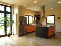 Spacious kitchen. Interior of spacious modern house: well-lit kitchen Royalty Free Stock Photography