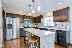 Spacious kitchen with chocolate brown cabinets. Spacious kitchen with open floor plan features chocolate brown cabinets and an island with granite counter top stock images