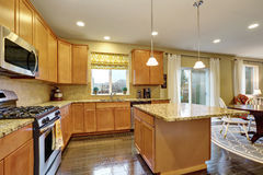 Spacious kitchen room with gleaming hardwood floor. Kitchen island and stainless steel appliances. Northwest, USA Stock Photo
