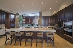 Spacious Kitchen With Stools At Island In House Royalty Free Stock Photos