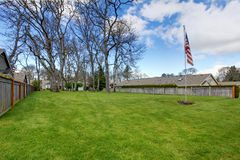 Spacious land area with green lawn and american flag Stock Image