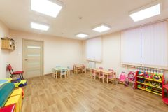 Spacious light pink colored game room with in the kindergarten.  Stock Photos