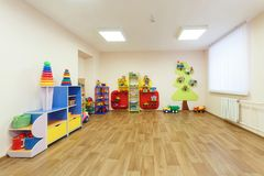 Spacious light pink colored game room with in the kindergarten.  stock photo