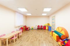 Spacious light pink colored game room with in the kindergarten.  Stock Image