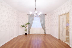 Spacious light room with chandelier and window. With curtains in new apartment Royalty Free Stock Image