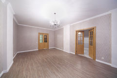 Spacious light room with wooden floor and opened doors Royalty Free Stock Image