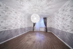Spacious light room with wooden floor and unusual chandelier Royalty Free Stock Image