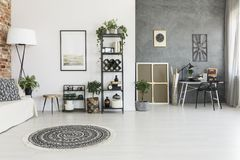 Spacious living room with carpet. Round patterned carpet in spacious living room with plants, poster and work area against grey wall Royalty Free Stock Photo