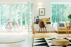 Spacious living room with pouf. Pouf on black and white carpet in spacious living room with bike and brown chair at desk with laptop Stock Photo