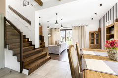 Spacious room with brick wall and stripes on the other side. Living room with garden view and stairs leading up stock images