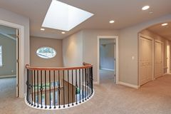 Spacious second landing with tan walls. Skylight and black hand rails overlooking grand entrance foyer stock photo