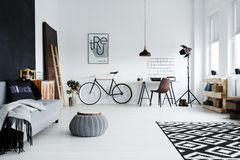 Spacious studio apartment. Modern spacious studio apartment with sofa, bike and desk Stock Image