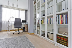 Spacious study room. With glass bookcase, chair, desk and large window Stock Photography