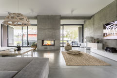 Spacious villa with cement wall. Spacious villa interior with cement wall effect, fireplace and tv Royalty Free Stock Images