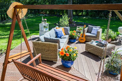 Spacious villa patio during summer. Spacious villa patio with garden swing, rattan firniture set, grill and guitar during summer stock photography