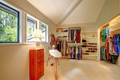 Spacious walk-in closet. With built-in shelves. Closet full of cloths, shoes. View of ironing board and small cabinet royalty free stock photos