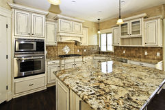 Spacious white luxury kitchen. Modern kitchen in luxury home includes custom wood cabinets with tile and custom stone countertops Royalty Free Stock Photo