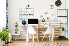 Spacious office for writer. Spacious white office space for a freelance writer with personal decorations and lots of plants royalty free stock photo
