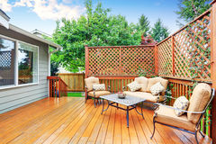 Spacious wooden deck with patio area and attached pergola. Royalty Free Stock Images