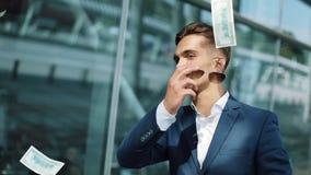Spada dolary na młodym szczęśliwym biznesmenie europejczyka spadać pieniądze podeszczowy niebo Biznes, ludzie i finanse pojęcie, zbiory wideo