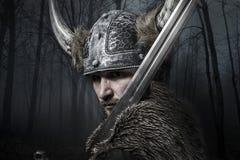 Spada, guerriero di Viking con il casco sopra il fondo della foresta Fotografia Stock