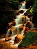 Spada kaskadą na strumieniu woda mineralna z żelaznym cedziny na zielonych mechatych głazach. Wczesny poranek w cieniach pod stary Zdjęcia Stock