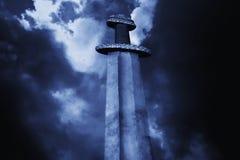 Spada medievale di vichingo contro un cielo drammatico immagine stock