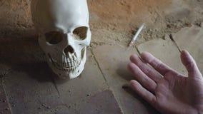 Spada ręka nieżywy nałogowiec z strzykawką przeciw tłu czaszki zwolnione tempo zbiory wideo