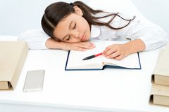 Spada uśpiony na lekci Dziewczyny dziecko spada uśpiony podczas gdy czytelniczej książki stołu bielu tło Uczennica męcząca studio zdjęcie royalty free