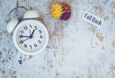 Spada Z powrotem światła dziennego oszczędzania czasu pojęcie z bielu zegarem i kwiatami, mieszkanie nieatutowy fotografia stock