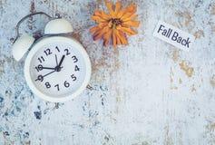 Spada Z powrotem światła dziennego oszczędzania czasu pojęcie z bielu zegarem i kwiatami, mieszkanie nieatutowy zdjęcie stock
