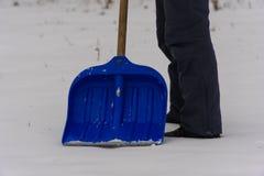 spade de mens verwijdert sneeuwschop De wintersneeuw stock afbeelding