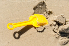 Spade digs wet sand. Playing on the beach in summer. Stock Photo