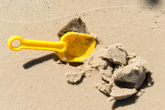 Spade digs wet sand. Royalty Free Stock Photo