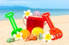 Spade en ander speelgoed op tropisch strand Royalty-vrije Stock Afbeeldingen