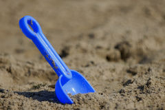 Spade waiting for kids 2. Blue Spade stucking in sand stock image