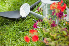 Spade and watering can by flowers at park Stock Photo