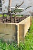 Planter for vegetable garden. Spade in a wooden  planter for vegetable garden Royalty Free Stock Image
