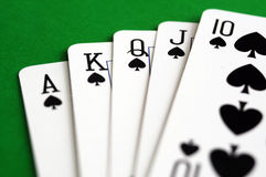 Spades royal flush. Poker playing cards, spades royal flush over green table Stock Images
