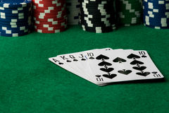 Spades straight flush. With poker chips on green table Royalty Free Stock Photography