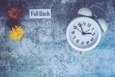 Spadku światła dziennego oszczędzania czasu pojęcie z bielu zegarem i kwiatami, mieszkanie nieatutowy obraz stock