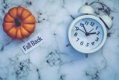 Spadku światła dziennego oszczędzania czasu pojęcie z bielu zegarem i kwiatami, mieszkanie nieatutowy obrazy stock