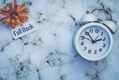 Spadku światła dziennego oszczędzania czasu pojęcie z bielu zegarem i kwiatami, mieszkanie nieatutowy zdjęcia royalty free