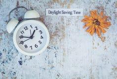 Spadku światła dziennego oszczędzania czasu pojęcie z bielu zegarem i kwiatami, mieszkanie nieatutowy fotografia stock