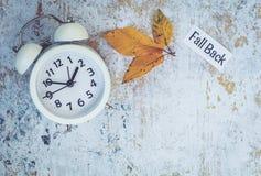 Spadku światła dziennego oszczędzania czasu pojęcie z bielu zegarem i kwiatami, mieszkanie nieatutowy fotografia royalty free