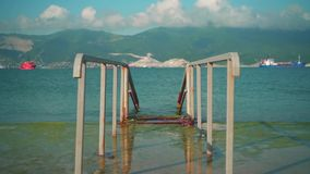 spadku morze Metal budowa na betonowej bazie Tło jest morzem, góry, chmury nad górami zdjęcie wideo